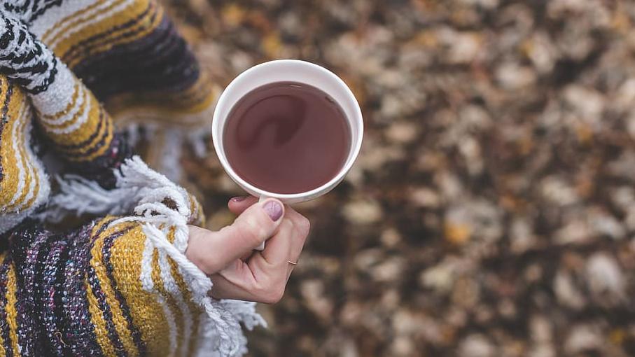 main d'une femme tenant une tasse chaude, dans un jardin en autombne