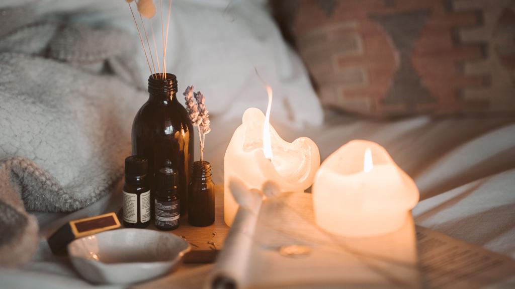 scène cocooning avec bougies et flacons d'huile que un lit.