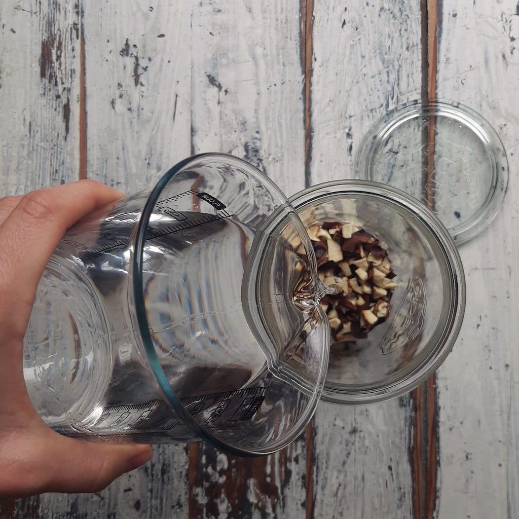 main qui verse l'alcool dans un pot,