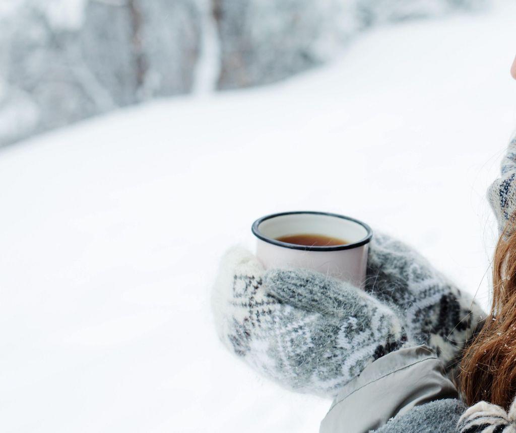une tasse chaude portée par une femme avec des gants